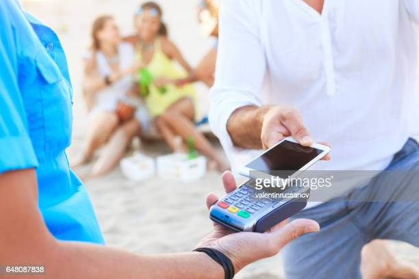 Young man using smart phone for contactless payment