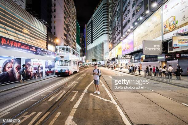 Young man using smart phone in city street at night