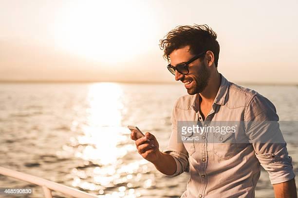 Junger Mann mit Smartphone auf einem Boot bei Sonnenuntergang.