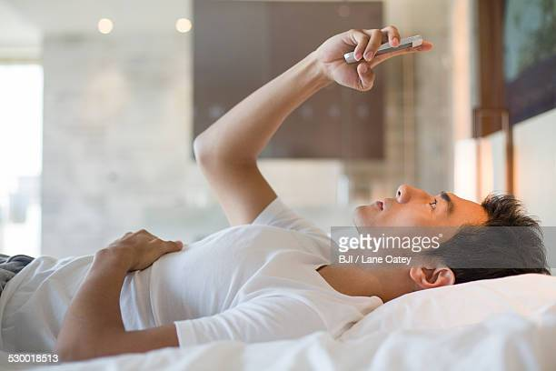 Young man using smart phone on bed
