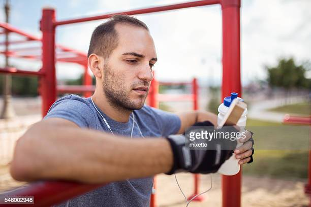 Young man using smart phone on training