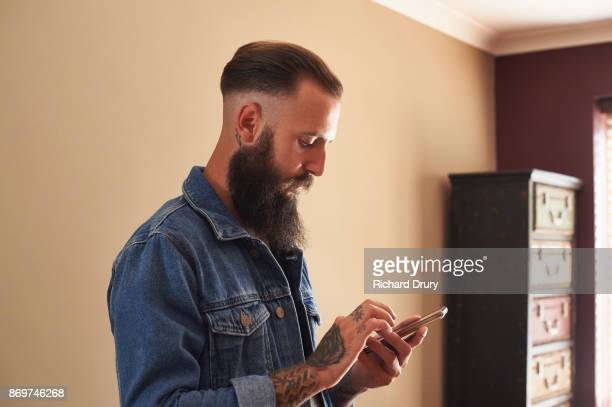 Young man using smartphone in his living room
