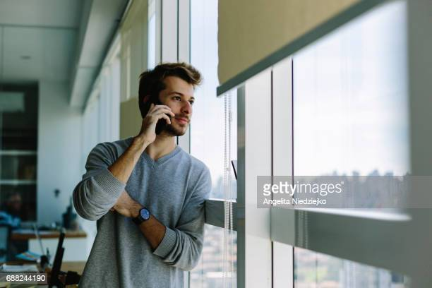 Young man using smartphone in office,