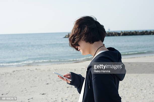 Young man using smartphone on the beach