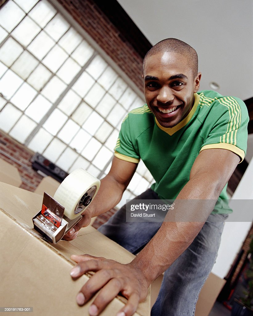 Young man using tape dispenser on box, portrait, low angle view : Stock Photo