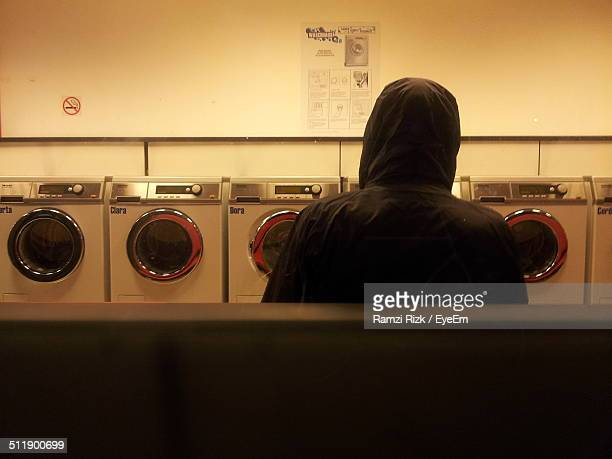 Young man waiting alone in coin laundry