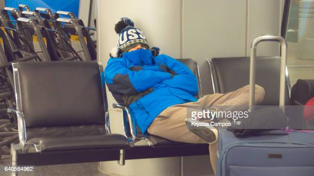 Young man waiting for flight at the airport lounge