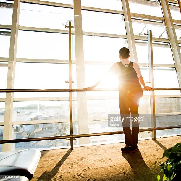 Young man waiting for flight in the airport