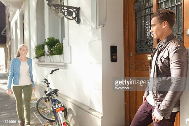Young man waiting for his girlfriend in front of a residential house