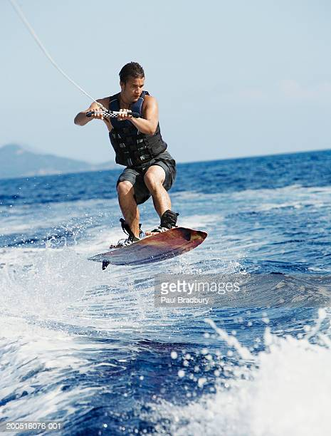Young man wakeboarding on coast