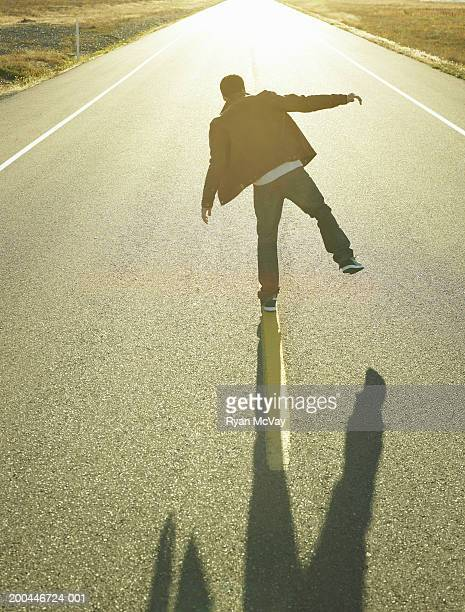 Young man walking along line in middle of road at sunset, rear view