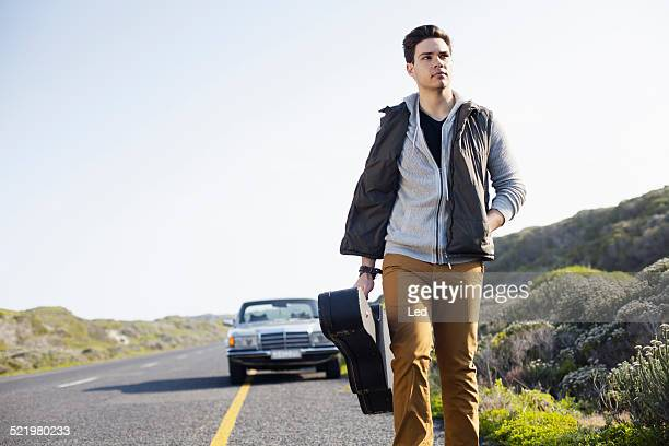 Young man walking along road with guitar case, Cape Town, Western Cape, South Africa