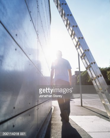 Young man walking along street, ladder in foreground, rear view : Stock Photo