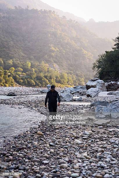 Young Man Walking At Riverbank In Forest surrounded mountain area at Ganga, Rishikesh