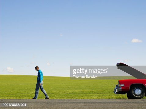 Young man walking away from car with hood up on side of road
