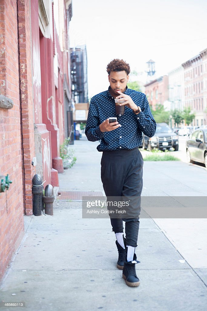 Young man walking down street with cellphone and drink
