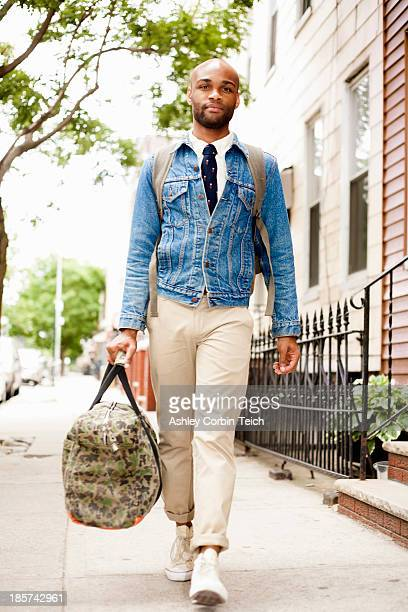 Young man walking down street with holdall