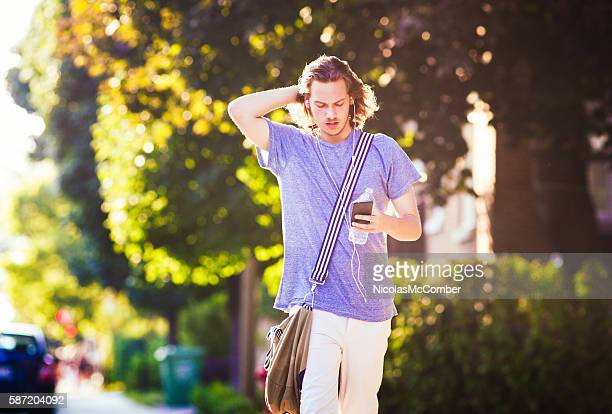 Young man walking home phone and water bottle in hand