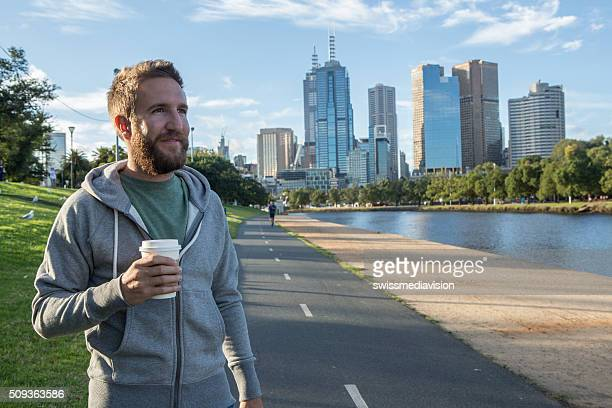 Young man walking in Melbourne city carries a takeaway coffee