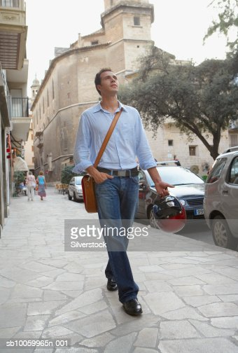 Young man walking in street : Stock Photo