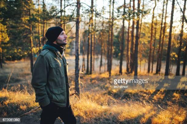 Jeune homme marche dans la belle forêt en plein air