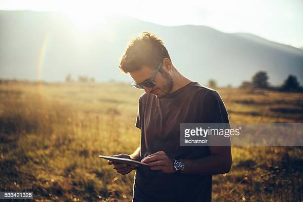 Junger Mann zu Fuß in der Natur, mit einem digitalen tablet