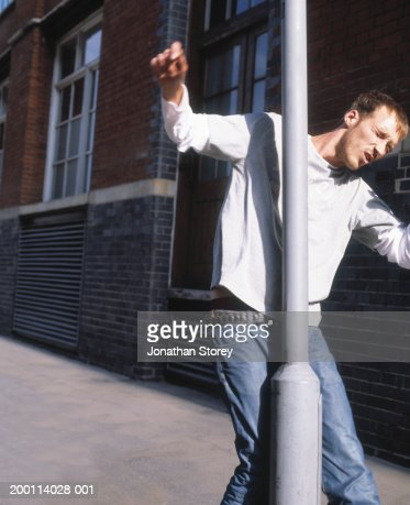 Young man walking into lamp post : Stock Photo