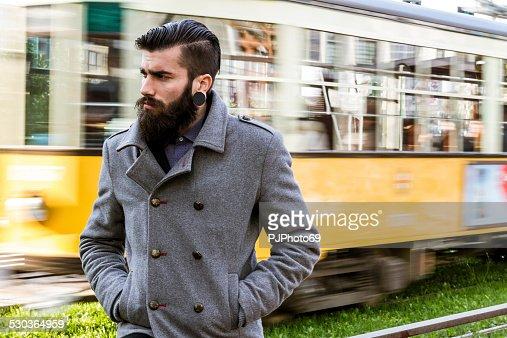 Young man (stylish hipster) walking near tramway