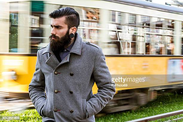 Young man (stylish hipster) walking near tramway