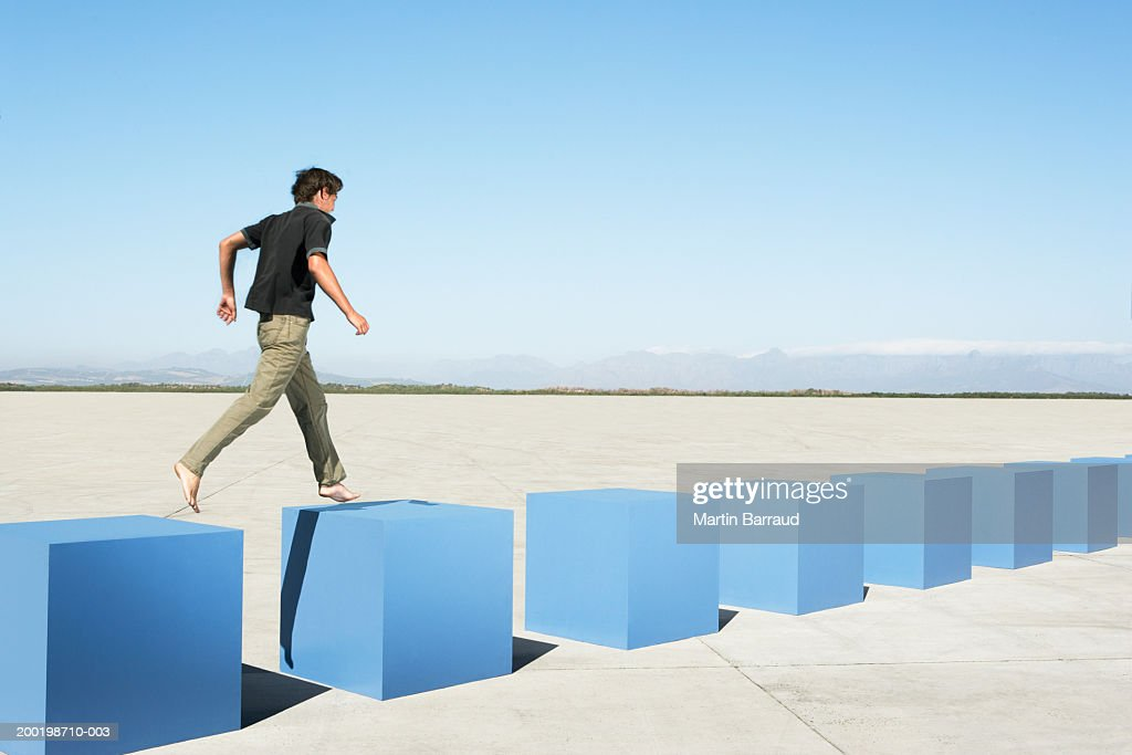 Young man walking on row of large cubes in barren landscape : Stock Photo