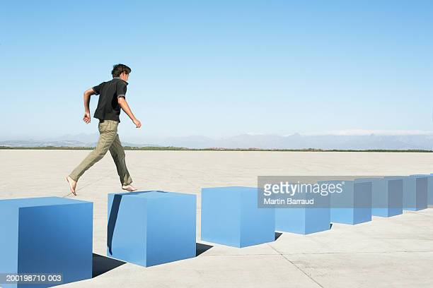 Young man walking on row of large cubes in barren landscape