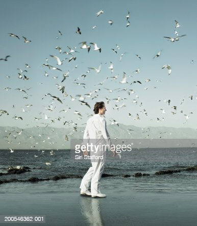 Young man walking on shore amongst flocks of birds (Digital Composite) : ストックフォト
