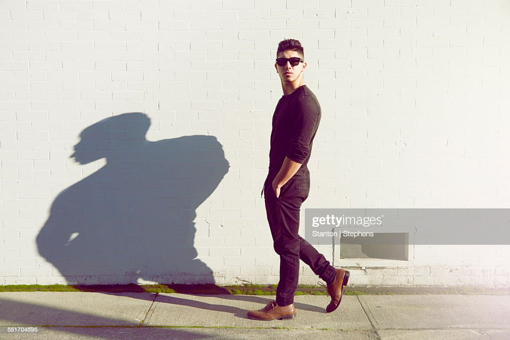 Young man walking past white wall
