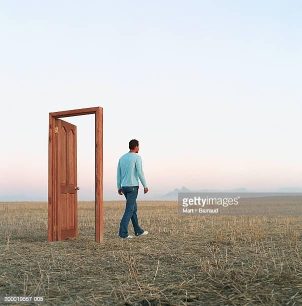 Young man walking through door in open landscape