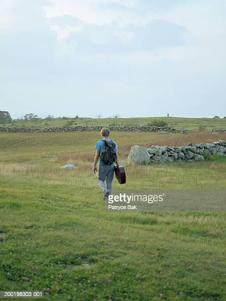 Young man walking through field with guitar case, rear view