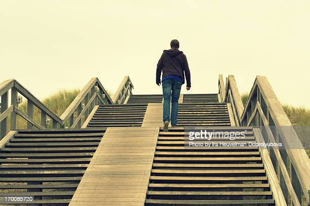 Young man walking up on big staircase