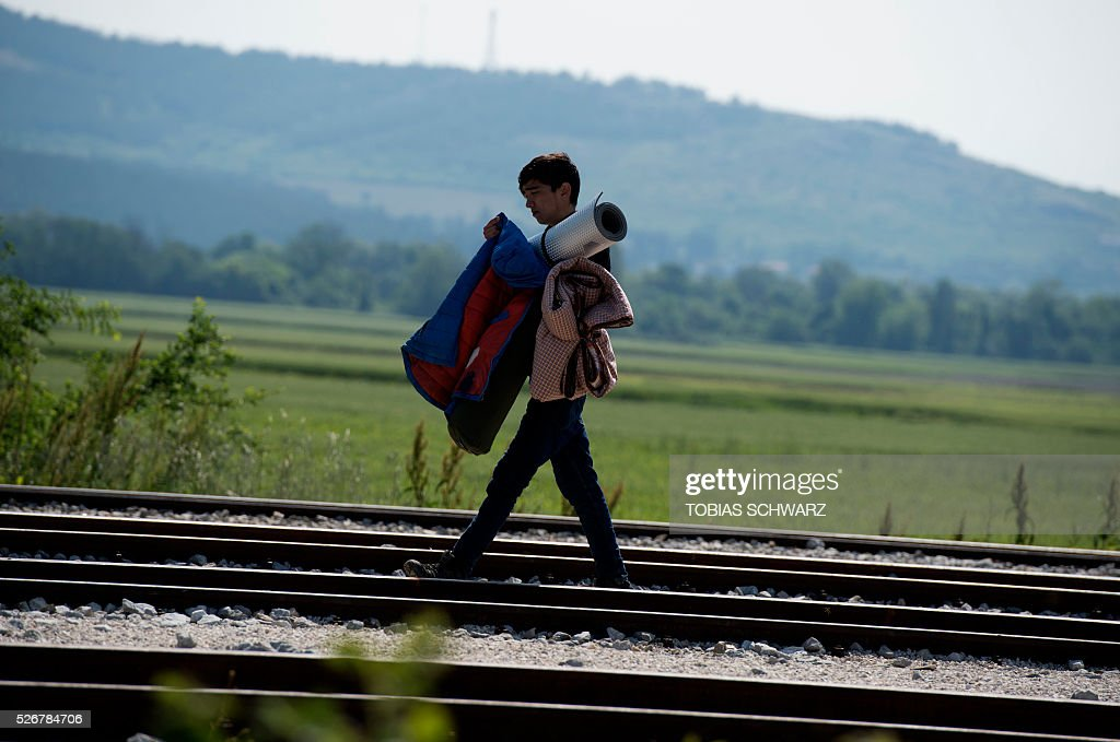A young man walks along rail tracks at a makeshift camp for migrants and refugees near the village of Idomeni not far from the Greek-Macedonian border on May 1, 2016. Some 54,000 people, many of them fleeing the war in Syria, have been stranded on Greek territory since the closure of the migrant route through the Balkans in February. / AFP / TOBIAS