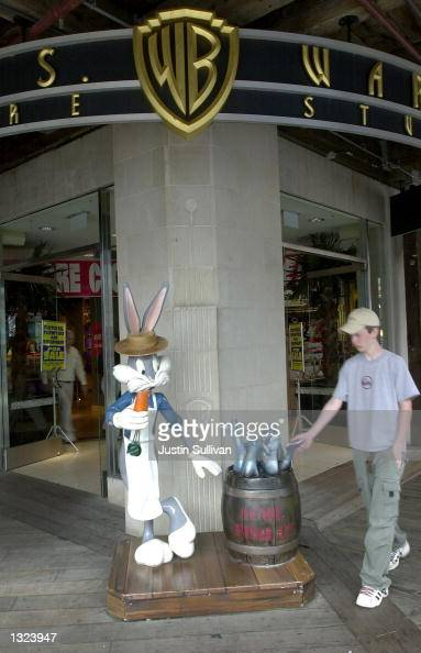 A young man walks by a statue of cartoon character Bugs Bunny dressed as a fisherman outside of a Warner Bros Studio Store July 9 2001 on Pier 39 in...