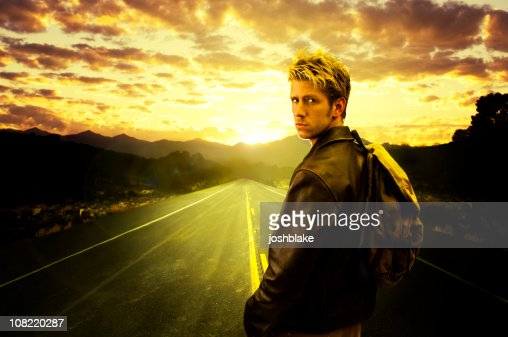 Young man Walks down road : Stock Photo