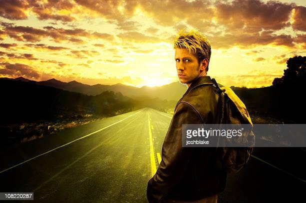 Young man Walks down road