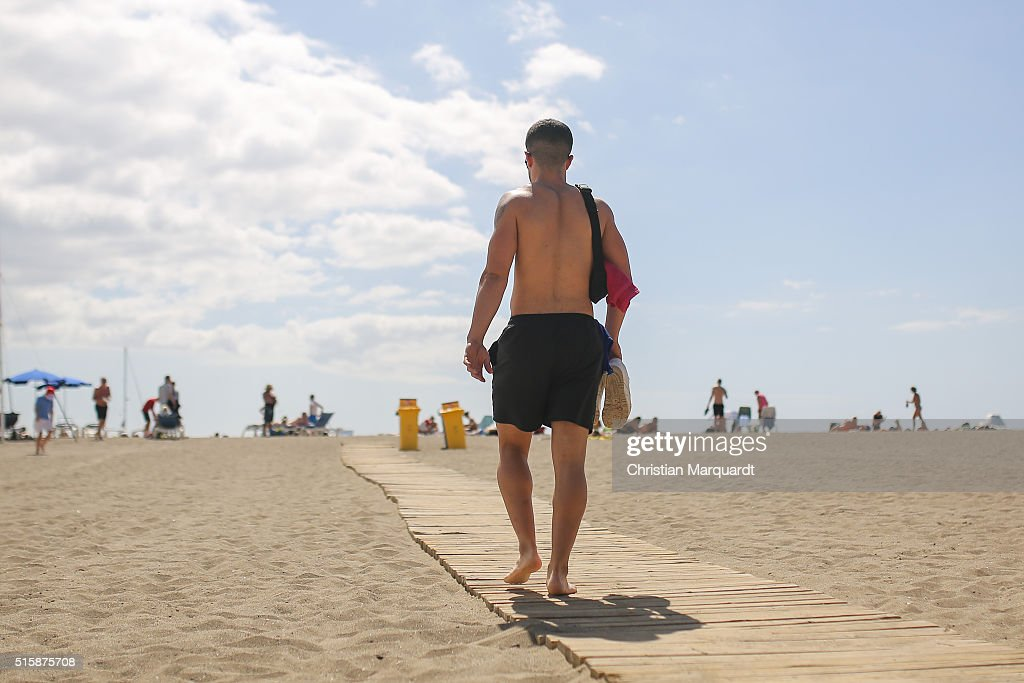 A young man walks over a samall wodden path on a white sandy beach next to Los Christianos which is made from sahara sand on February 24 in Tenerife...