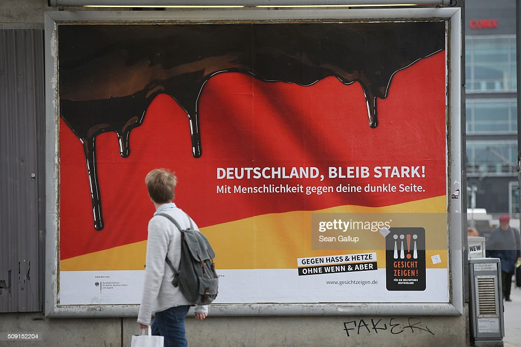 A young man walks past a poster showing the German flag with a dripping black portion and that reads: 'Germany, stay strong! With humanity against your dark side,' and below: 'Against hate and baiting, no if and but' on February 9, 2016 in Berlin, Germany. The poster is part of a campaign supported by Germany's Ministry for Families, Seniors, Women and Youth in an effort to encourage more tolerance, particularly of the 1.1 million migrants and refugees that arrived in Germany in 2015. Though a majority of Germans have shown a strong willingness to accept the newcomers and thousands have volunteered to help them, the country has also seen a growing number of attacks, including beatings, arson, vandalism and other violence against refugees and refugee shelters.