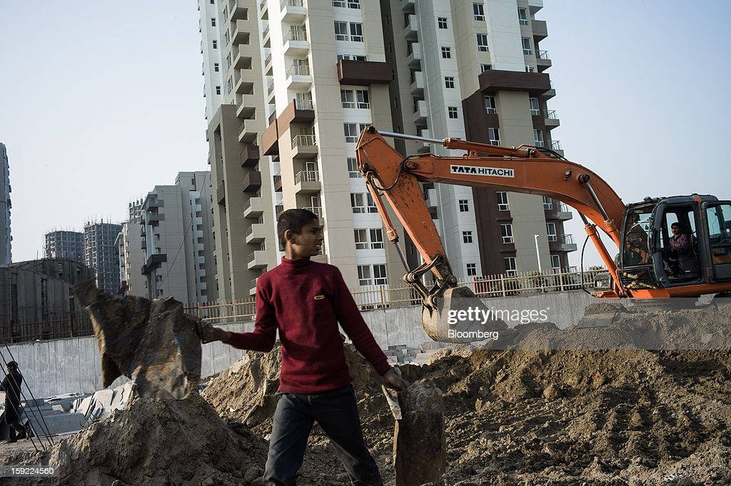 A young man walks past a Tata Hitachi Construction Machinery Co. excavator at a construction site in Noida, Uttar Pradesh, India, on Wednesday, Jan. 9, 2013. India's Finance Ministry predicts GDP growth of as little as 5.7 percent in the year to March 31, the least in a decade. Photographer: Sanjit Das/Bloomberg via Getty Images
