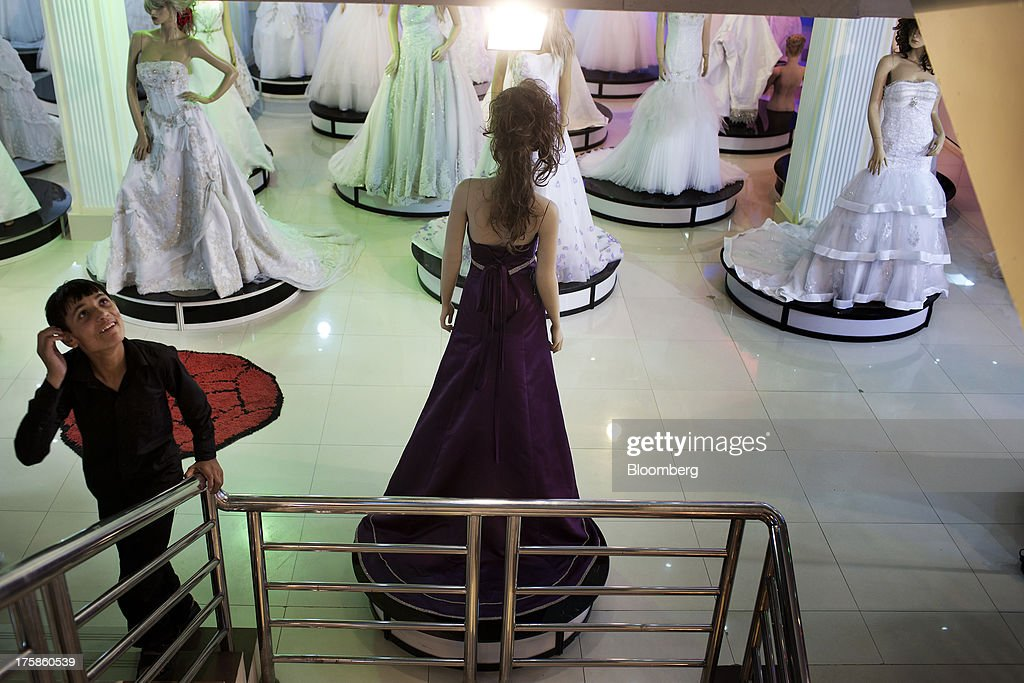 A young man walks past mannequins displaying evening wear inside a department store in the Faisal Business Center in Kabul, Afghanistan, Wednesday, Aug. 7, 2013. A smooth U.S. exit from Afghanistan will depend on Pakistans cooperation with the logistical pullout, as well as its backing for peace talks in neighboring Afghanistan and an end to any support for extremist proxies operating there. Photographer: Victor J. Blue/Bloomberg via Getty Images