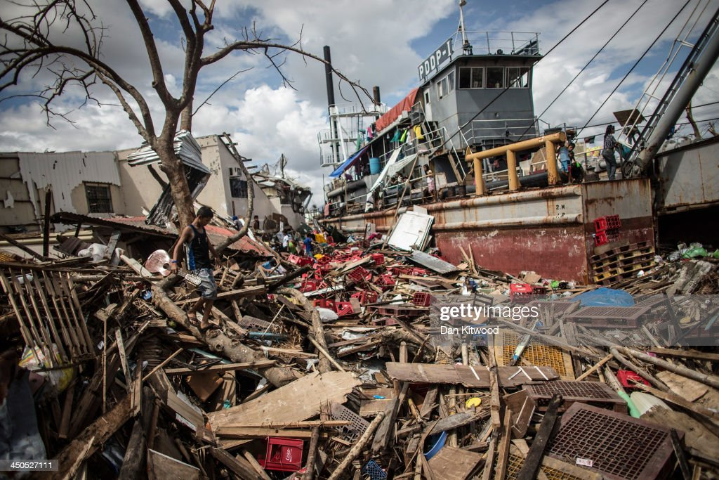 A young man walks through debris with a broken guitar towards a tanker where he is sleeping in a particularly badly damaged part of Tacloban on...