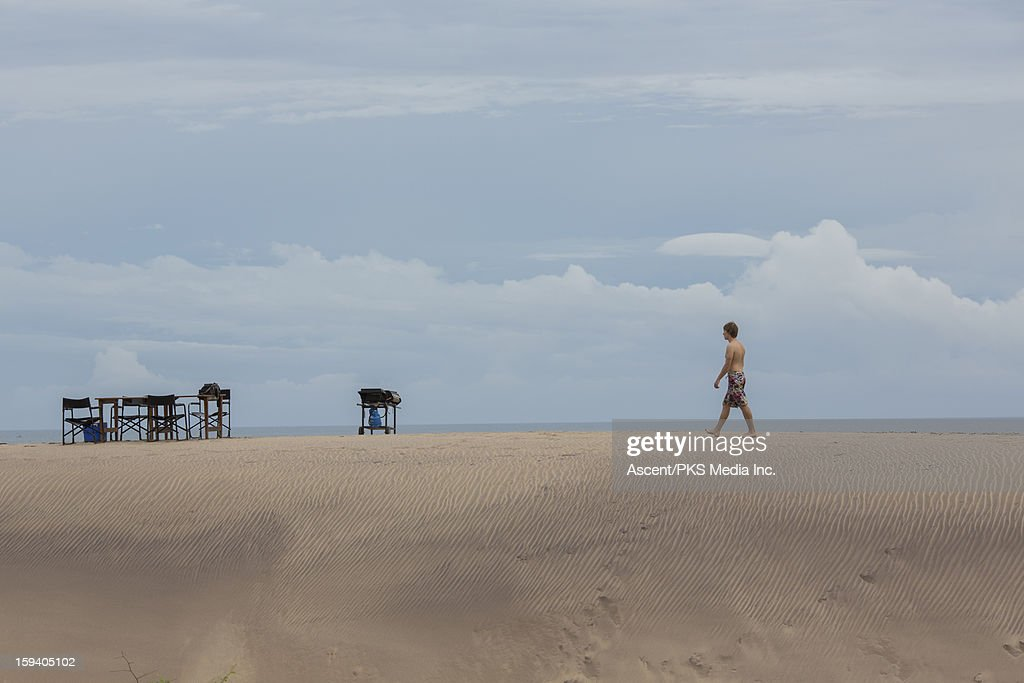 Young man walks to table setting on sand dune : Stock Photo