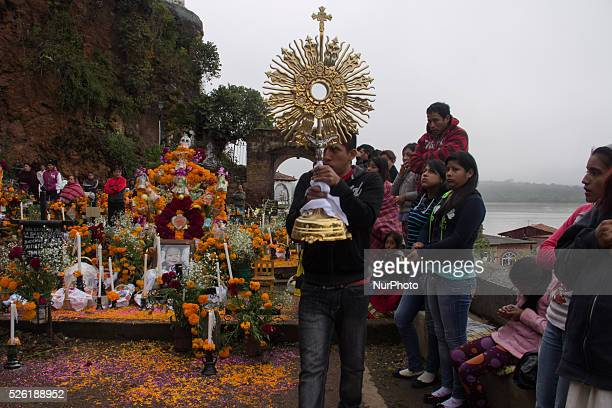 A young man walks with a ciborium for Mass held in the cemetery of Janitzio on November 1 2015