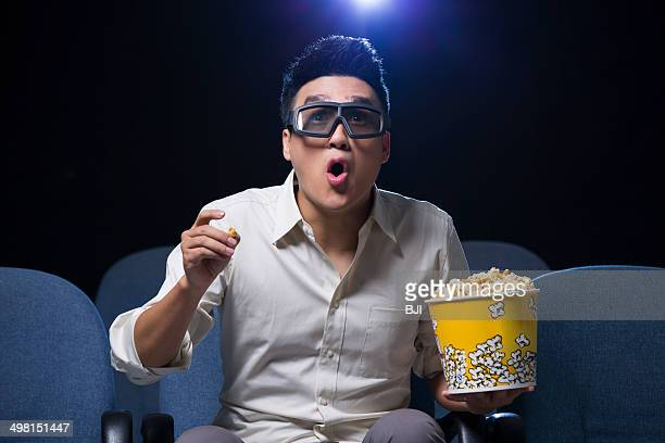 Young man watching 3D movie in cinema