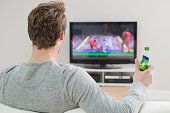 Young man watching football on television with beer bottle