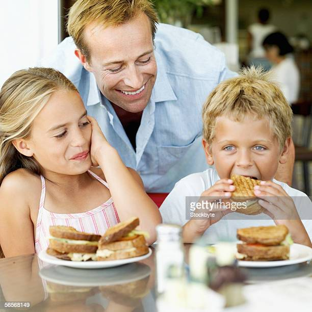 young man watching his children eat toasted sandwiches